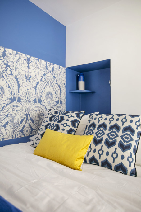 furnished studio sleeping area blue wallpaper