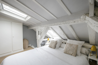 furnished Paris apartment wooden beams painted white