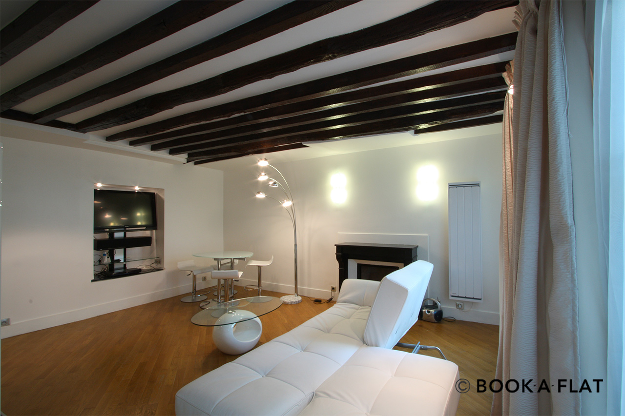 Living room with sofa, coffee table, dining area and exposed beams