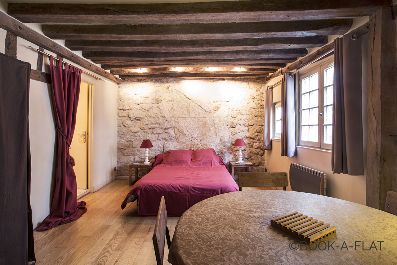 Bed area with exposed beams and stonework